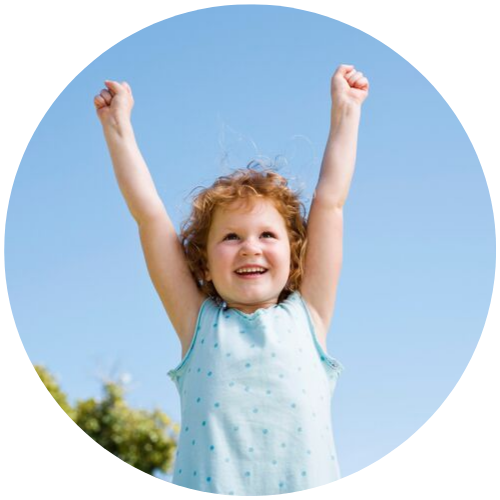 a little girl with her hands raised to the sky and looking happy